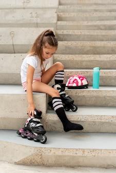 Vue de côté, fille, patins à roues alignées