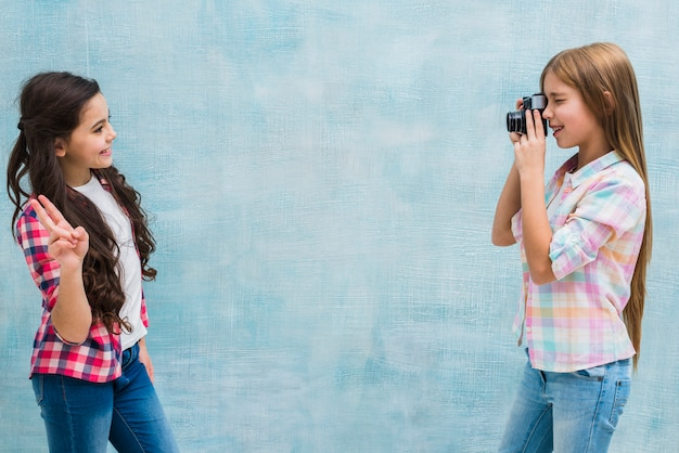Vue côté, de, a, fille, prendre, photo, de, elle, amie, geste paix