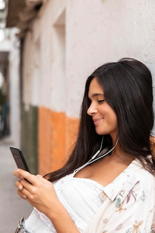 Vue de côté fille souriante portant des écouteurs