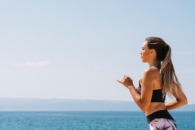 Vue côté, de, a, fitness jeune, femme, courant, devant, mer