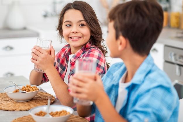 Vue de côté des frères et sœurs buvant du jus de fruits frais