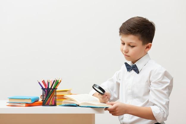Vue côté, garçon, bureau, lecture