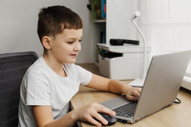 Vue de côté garçon une maison à l'aide d'un ordinateur portable