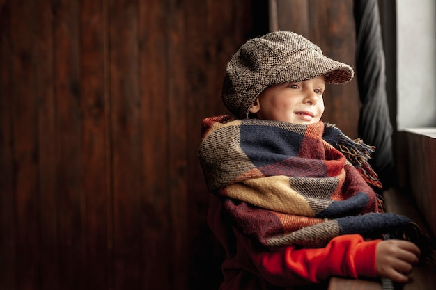 Vue de côté garçon mignon avec bonnet et écharpe
