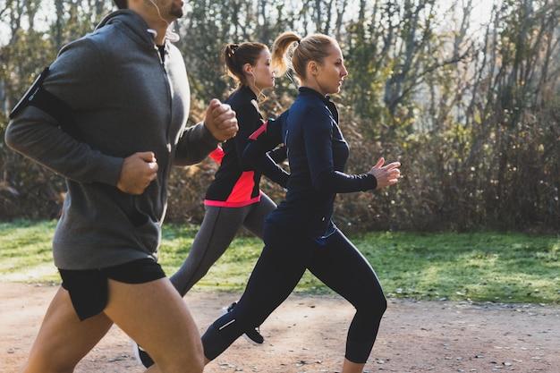 Vue de côté de gens qui courent dans le parc