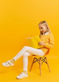 Vue côté, de, girl, poser chaise, pendant, lecture livre