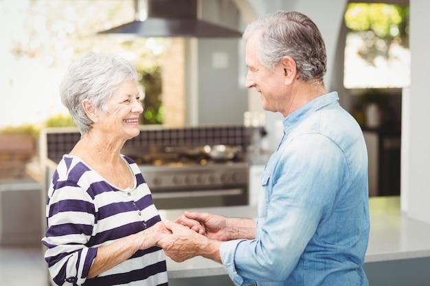 Vue côté, de, heureux, couples aînés, tenant mains