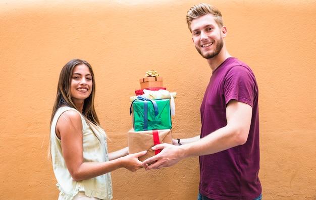 Vue côté, de, a, heureux, jeune couple, à, pile cadeaux