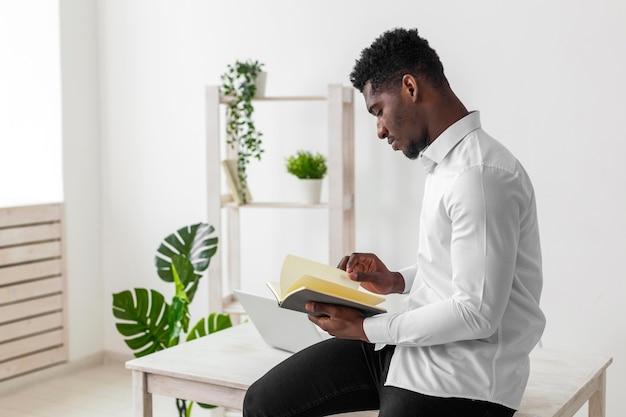 Vue côté, homme américain africain, lecture