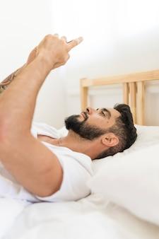 Vue côté, de, a, homme, coucher lit, tenant, téléphone portable