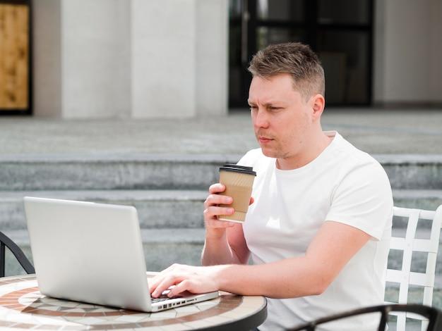 Vue côté, de, homme, dehors, avoir café, et, travailler, ordinateur portable