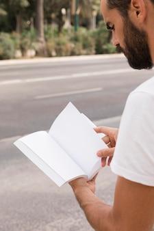 Vue côté, de, homme, dehors, lecture livre