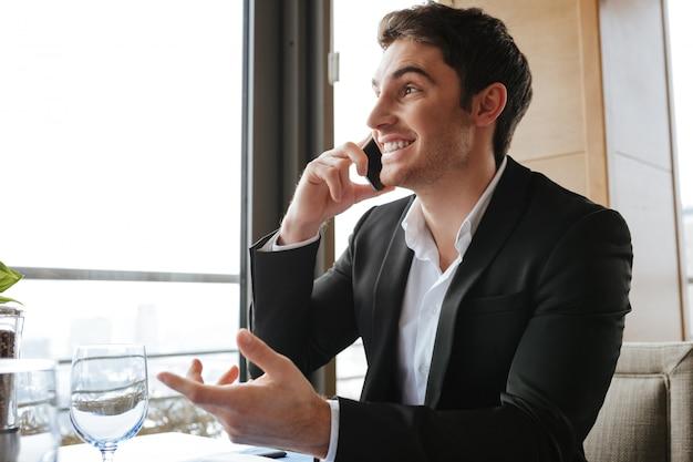 Vue côté, de, homme heureux, dans, restaurant, conversation téléphone