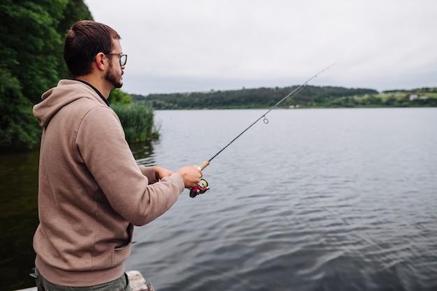 Vue de côté de l'homme de pêche dans le lac idyllique