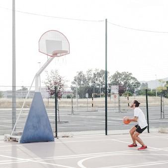 Vue côté, de, a, homme, préparer, lancer, basket-ball, dans cerceau
