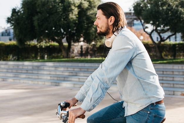 Vue de côté d'un homme à vélo dans le parc