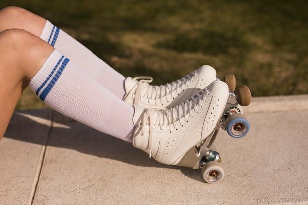 Vue de côté d'une jambe de femme avec un patin à roulettes blanc
