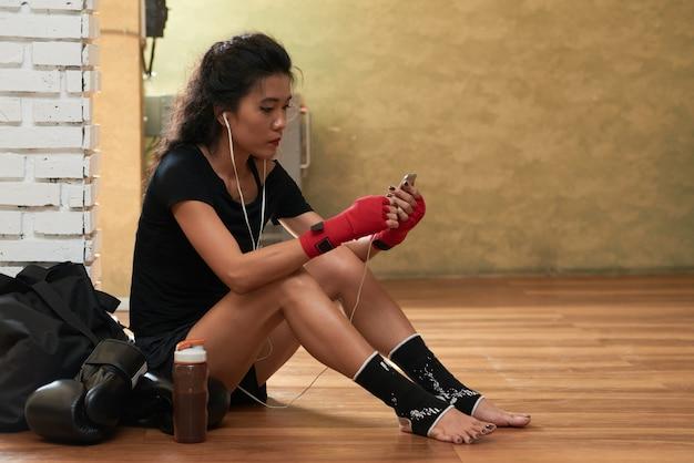 Vue côté, de, jeune, athlète femme, écouter musique, après, entrainement