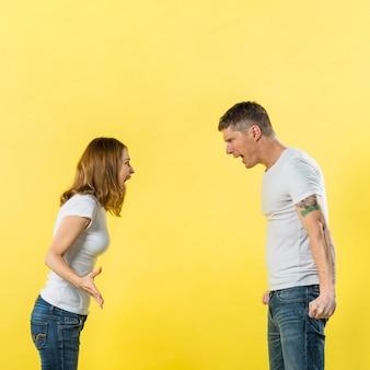 Vue côté, de, jeune couple, gronder, à, autre, sur, jaune, fond