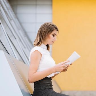 Vue côté, de, jeune femme affaires, lecture, documents, sur, campus bureau