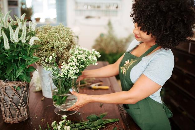 Vue côté, de, a, jeune femme, arranger, bouquet, de, fleurs blanches, dans, vase