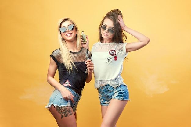 Vue de côté de la jeune femme branchée dans des lunettes et des shorts debout et fumer