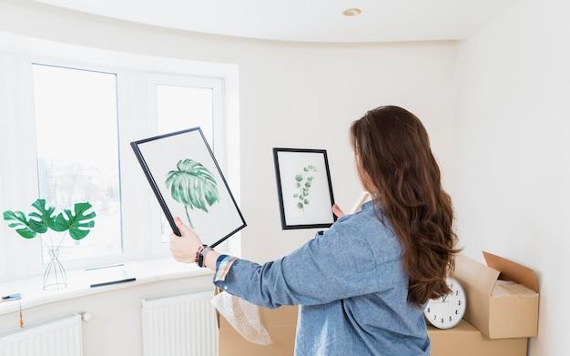 Vue de côté d'une jeune femme choisissant un cadre photo pour sa nouvelle maison