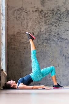 Vue de côté d'une jeune femme faisant des exercices d'étirement sur un tapis de yoga