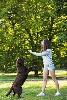 Vue de côté d'une jeune femme jouant avec son chien dans le parc
