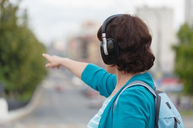 Vue côté, jeune femme, marche, dans ville, contre-jour, écoute, musique, écouteurs