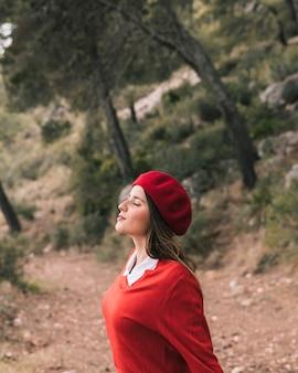 Vue de côté d'une jeune femme profitant de la nature