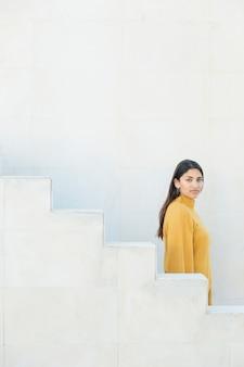 Vue de côté d'une jeune femme regardant la caméra debout près d'un escalier