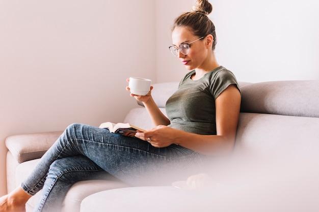 Vue côté, de, a, jeune femme, s'asseoir divan, livre lecture