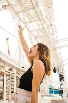 Vue de côté de la jeune femme se moquer au parc d'attractions