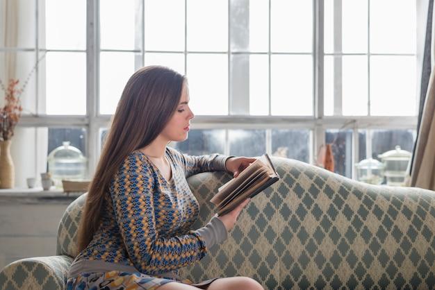 Vue côté, de, a, jeune femme, séance, devant, fenêtre, livre lisant
