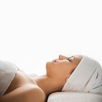 Vue côté, de, jeune femme, à, serviette enveloppée, sur, tête, dormir, sur, lit massage, contre, toile de fond blanc