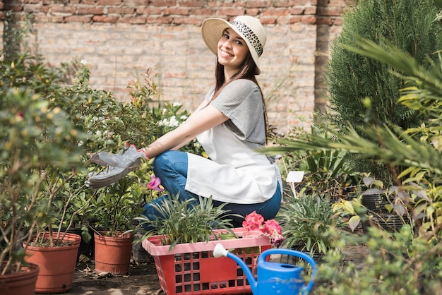 Vue de côté d'une jeune femme souriante prenant soin des plantes en serre