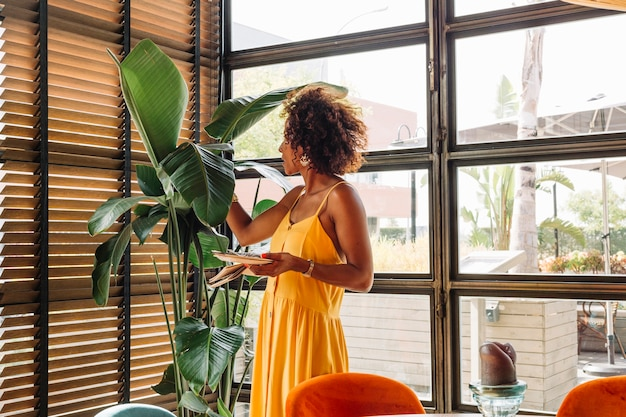 Vue côté, de, jeune femme, tenant plaque, debout, près, les, plante