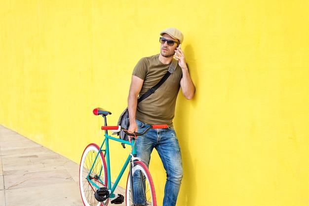 Vue de côté d'un jeune homme adulte avec un vélo vintage et portant des vêtements décontractés