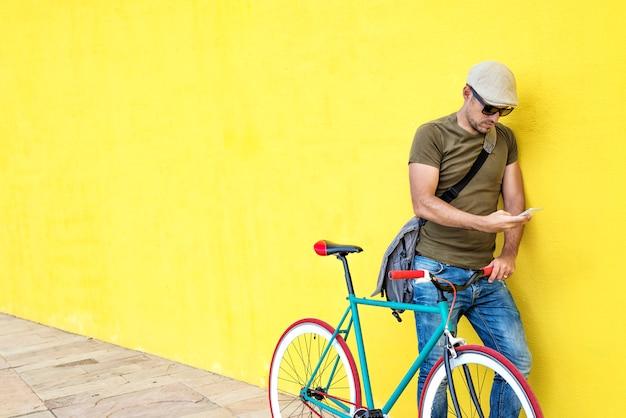 Vue de côté d'un jeune homme adulte avec un vélo vintage