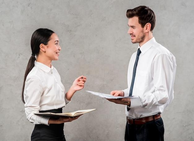 Vue côté, de, a, jeune homme affaires, et, femme affaires, discuter, de, projet, debout, contre, mur gris