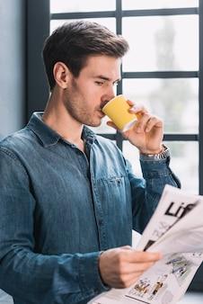Vue côté, de, a, jeune homme, boire café, pendant lecture journal