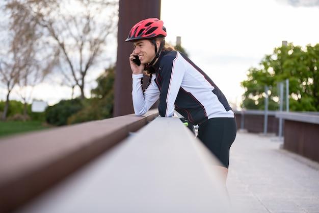 Vue côté, de, jeune homme, dans, casque, et, vêtements de sport, sourire, et, avoir, conversation smartphone, debout, sur, pont, pendant, entrainement vélo, dans, parc
