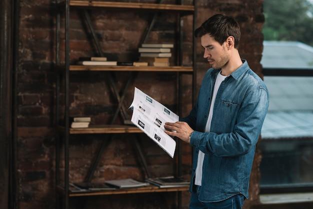 Vue de côté d'un jeune homme lisant un magazine à la maison