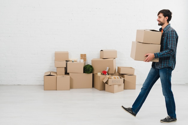 Vue côté, de, a, jeune homme, porter, cartons, dans main, marcher, dans chambre