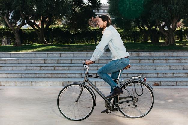 Vue de côté d'un jeune homme à vélo dans le parc