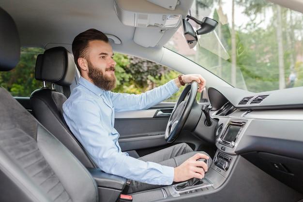 Vue de côté d'un jeune homme en voiture