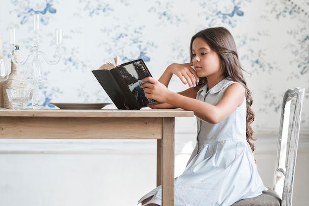 Vue de côté d'un livre de lecture fille à la table à manger
