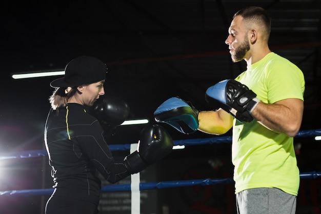 Vue côté, de, mâle, entraîneur, pratiquer, à, femme, boxeur, dans, gants protecteurs