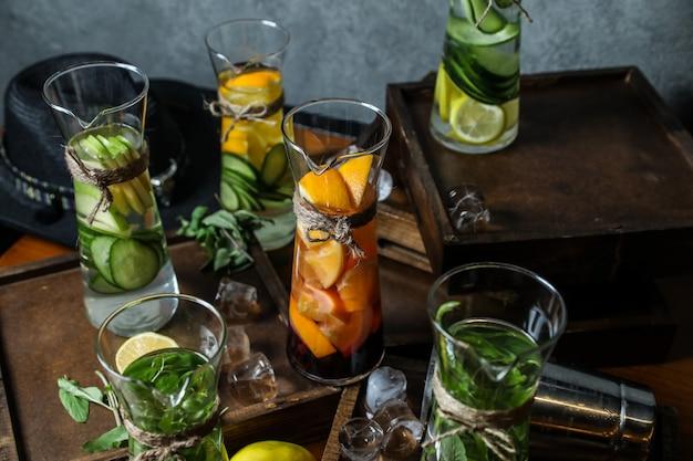 Vue de côté mélanger de l'eau de désintoxication avec des pommes au citron menthe et concombre dans des carafes